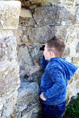 The boy looks through binoculars