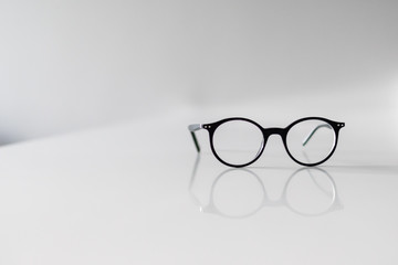 Black Eyeglasses closeup. Eye glasses.Modern style eyeglasses. Round glasses with transparent lenses. Vintage Glasses on white background. Close up eyeglasses with blurry technique.Fashion accessories
