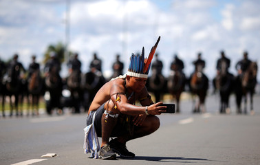 A member of the Indigenous population takes a picture in front of riot police during a protest against the Indigenous policies of the government of Brazilian President Michel Temer, in Brasilia