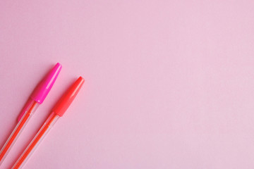 two pens on a pink background education concept