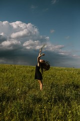 Woman in A Field with Storm Clouds in Summer