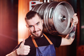 young handsome brewer man with a barrel of beer