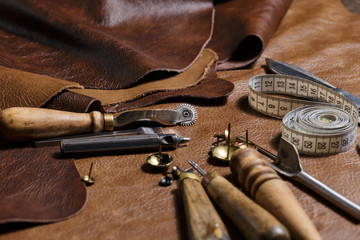 Leather craftman's work desk. Pieces of leather and working tools in the tailoring workshop.