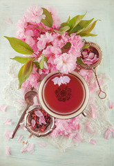 vintage, antique cup of fruit tea decorated with cherry flowers on white background in a shabby chic look