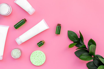 Cosmetics for skin care with natural ingredients. Eco cosmetics. Cream, lotion, oil, tonic near young green leaves on pink background top view copy space
