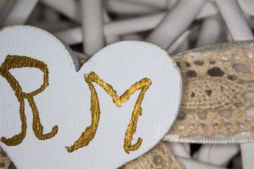 Homemade decorations for the wedding. The initials of the colored grooms of gold, on a wicker basket in the shape of a heart where to put dragees.