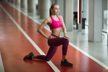 beautiful young girl in pink top with a stretcher in the gym