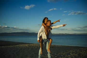 Man carries woman in white dress on back, couple happy on vacation. Couple in love stand on beach pointing in same direction. Couple have fun, sea and skyline background. Wedding, just married concept