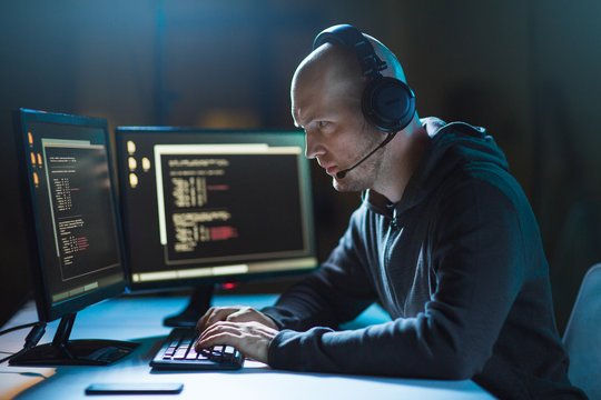 cybercrime, hacking and technology concept - male hacker with headset and coding on computer screen wiretapping or using computer virus program for cyber attack in dark room