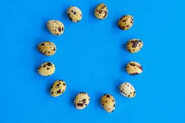 twelve quail eggs stacked around a circle with a place under the text in the center on a blue background