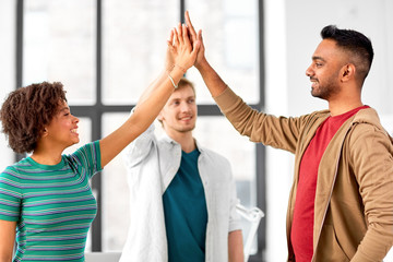 business, teamwork and corporate concept - happy creative team making high five at office
