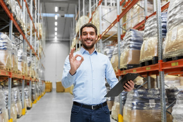 wholesale, logistic, business, export and people concept - happy man or manager with clipboard at warehouse showing ok hand sign