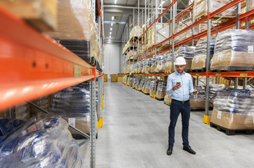 wholesale, logistic business, technology and people concept - businessman in helmet with smartphone and clipboard at warehouse
