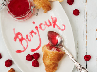 Close view of fresh croissants served with ripe raspberries and raspberry jam on white plate with lettering Bonjour over wooden surface.