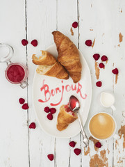 Top view of fresh croissants served with ripe raspberries and raspberry jam on white plate with lettering Bonjour over wooden background
