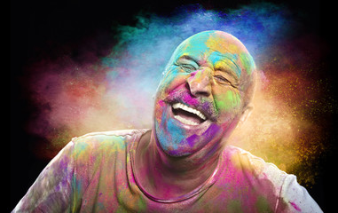 Bald smiling man with colorful face having fun. Colors festival