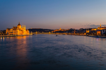 Budapest city at blue hour with illuminated Hungarian Parliament, Chain Bridge, Buda Castle, Fishermen's Bastion and Gellert Hill along Danube River, picturesque evening cityscape.