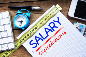 Salary expectation or requirement concept with math book on wooden desk