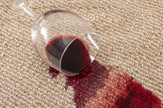 Home mishap and domestic accident concept with close up of  a spilled glass of red wine on brown carpet