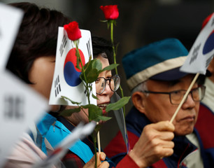 People wave South Korean flags and flowers as a convoy transporting South Korean President Moon Jae-in leaves the Presidential Blue House for the inter-Korean summit in Seoul
