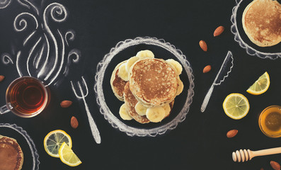Stack of pancakes with banana, lemon and almond  on chalk board with drawings