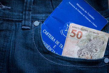 Brazilian portfolio of work and a hundred real banknotes in jeans pocket
