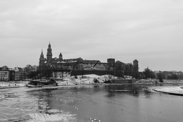 Snowy winter view of Wawel Castle seen from across the Vistula River. Its a cold, cloudy day.Krakow, Poland. Black and white