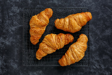 Croissants on a cooling rack on textured dark background, top view.