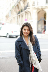 Chinese young girl standing in street background, walking after classes. Concept of international students and strolling in city.