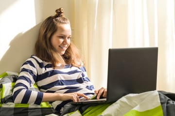 Teenage girl is studying at home, uses laptop