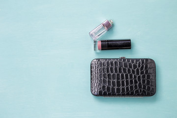 Design black shiny leather purse with lipstick stick and a bottle of perfume on blue wood texture background