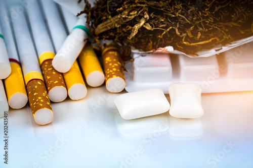 Nicotine chewing gum near pile of cigarettes and tobacco on