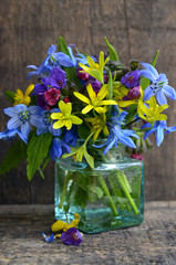 Сolorful spring flowers in a glass vase on old wooden background with space for text.Mother's Day,Birthday or Springtime greeting card concept. Selective focus.