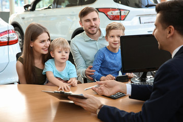 Young family with salesman sitting at table in dealership. Buying new car