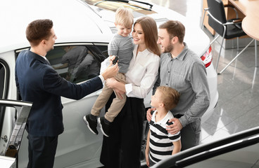 Salesman giving car key to young family in salon