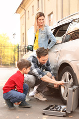 Young father with cute boy changing wheel, outdoors