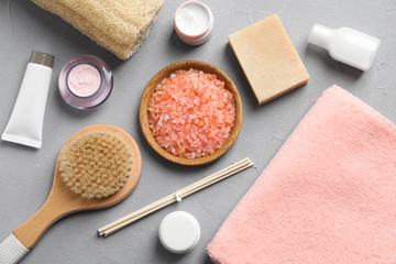 Flat lay composition with spa cosmetics and towel on grey background