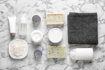 Flat lay composition with spa cosmetics and towel on light background
