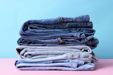 A perfect stack of jeans of different colors on a light background. minimalism, design,