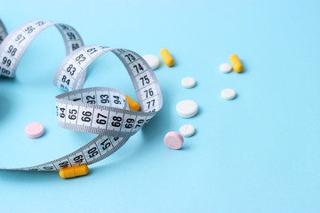 centimeter tape and pills on a pastel background with space for text. concept diet, burn fat and calories, weight loss. Bioadditives.
