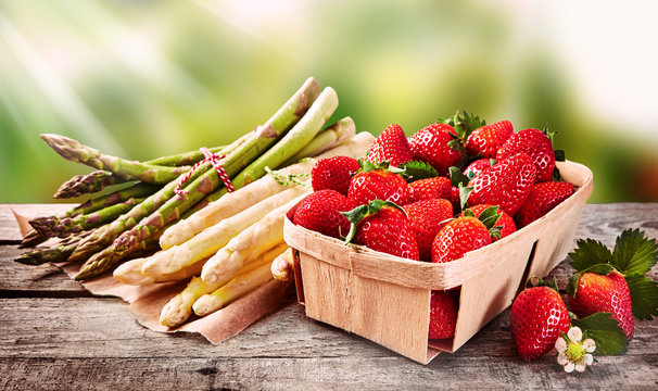 Wooden punnet of strawberries with fresh asparagus