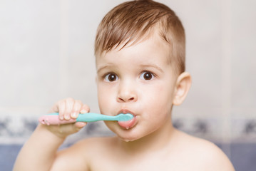 lovely baby brushing his teeth with a toothbrush in the bathroom