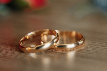 Beautiful picture with wedding rings lie on a wooden surface against the background of a bouquet of flowers