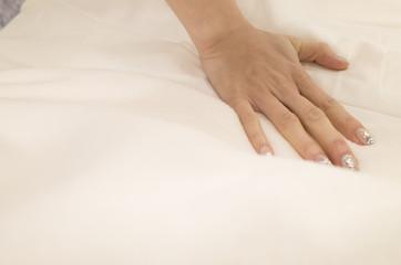 ベッドのクッション性を確かめる女性。