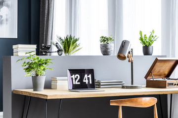 Side angle of a wooden desk with a laptop showing time, plant, lamp, books and phonograph standing by the window