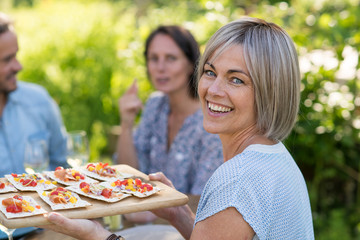 In summer. Group of friends gathered around a table in the garden to share a meal. a beautiful woman serves them appetizers on a platter while looking at the camera.