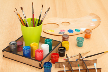 Palette and box with colorful paints and cup with paintbrushes