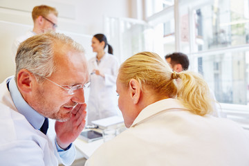Chefarzt flüstert in einem Meeting