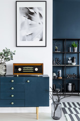 Painting, blue cabinet, retro radio, glass vase with branches, and metal shelf in the background