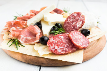Spoed Fotobehang Voorgerecht Tagliere con formaggio fresco, pane carasau, prosciutto crudo, salame e olive